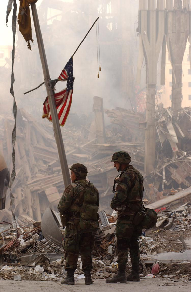 Two New York Army National Guardsman Stan's beneath a tattered American Flag in the wreckage of the World Trade Center, Septembe